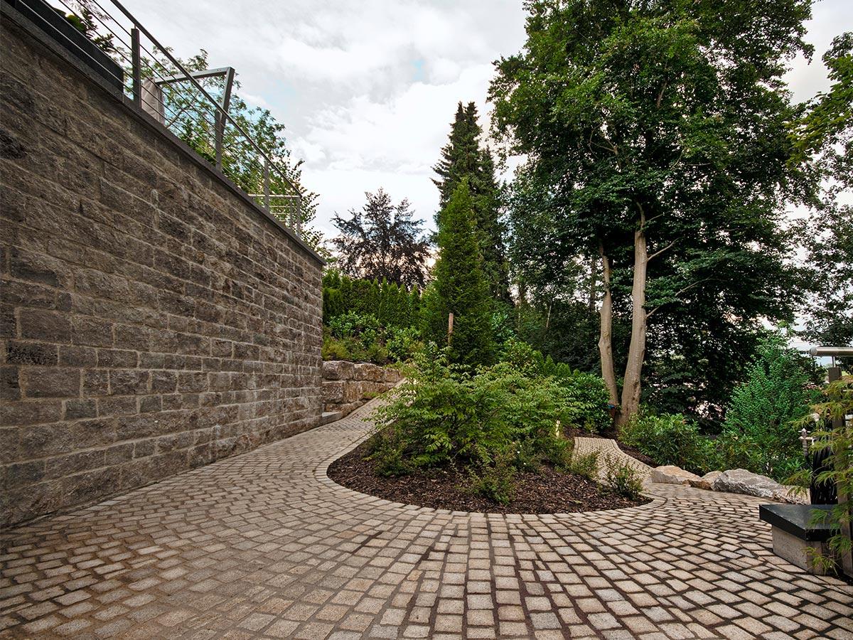 Ansprechende Steinmauer und gepflasterter Gartenweg - erstellt von der Firma bendl
