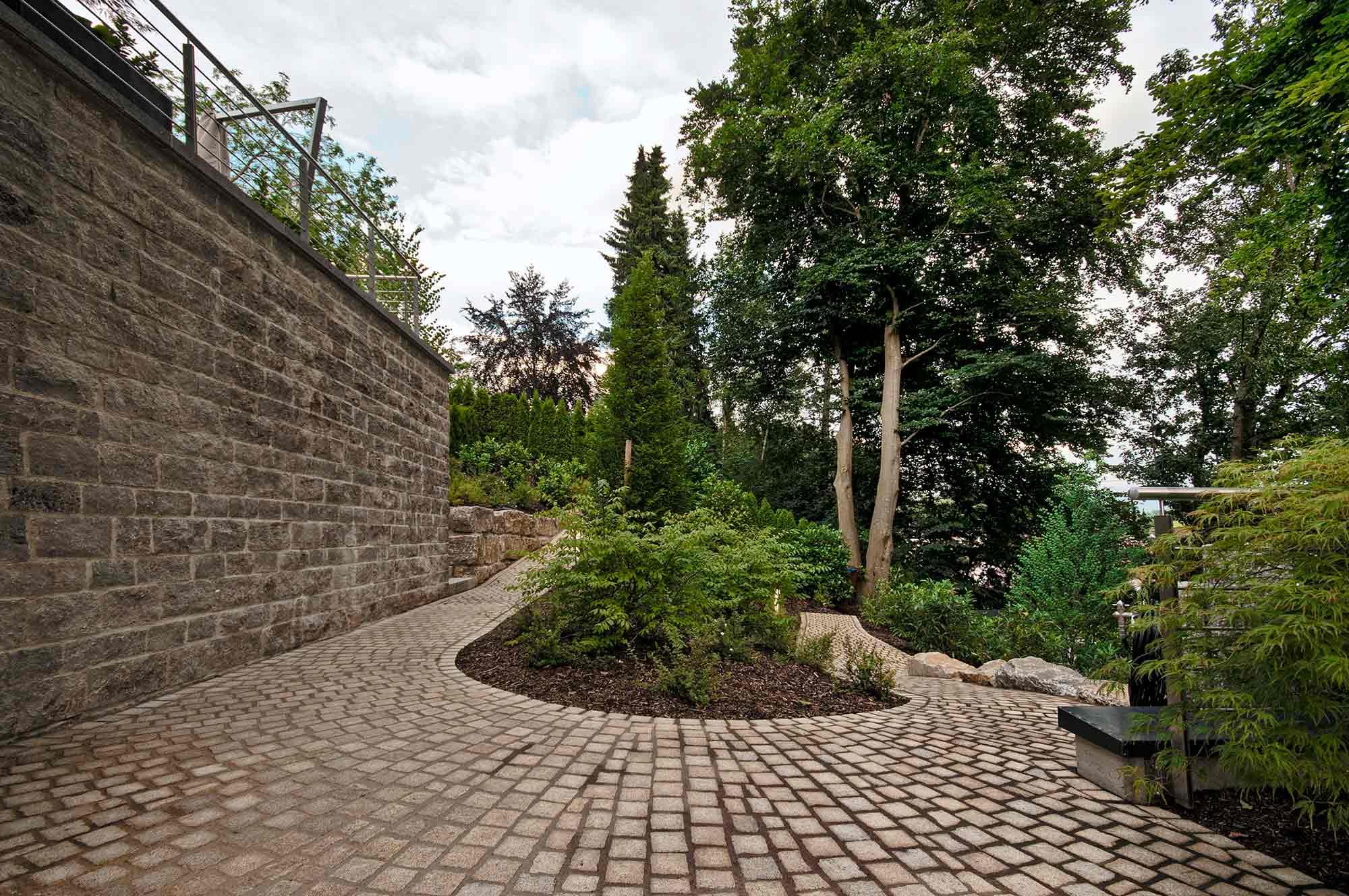 Ansprechende Steinmauer und gepflasterter Gartenweg