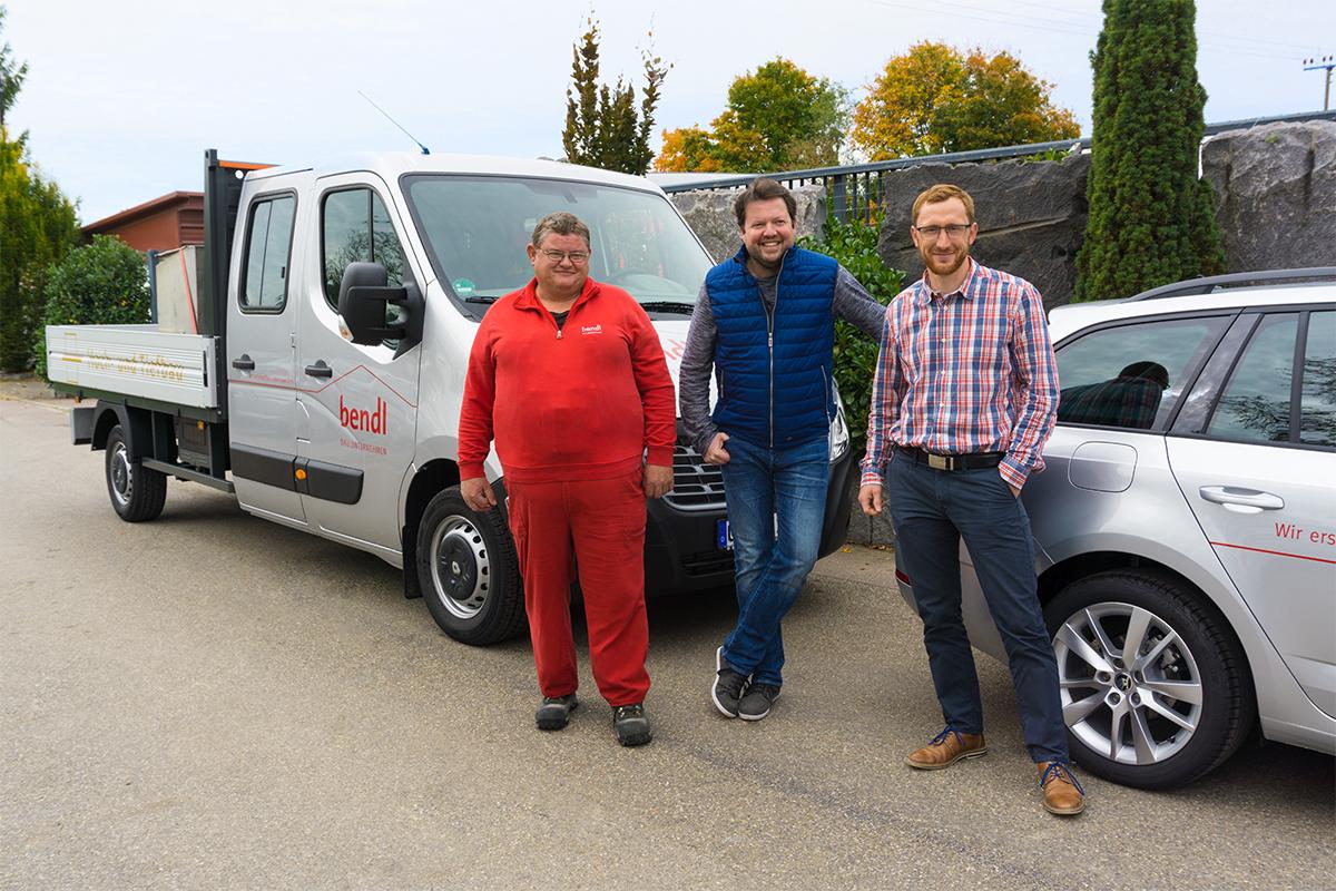 Kaufmännischer Leiter Erik Romer übergibt feierlich an Konrad Beck sein neues Tiefbau-Pritschenfahrzeug sowie an Schlüsselfertig-Projektleiter Michael Maurer sein neues Firmenfahrzeug.