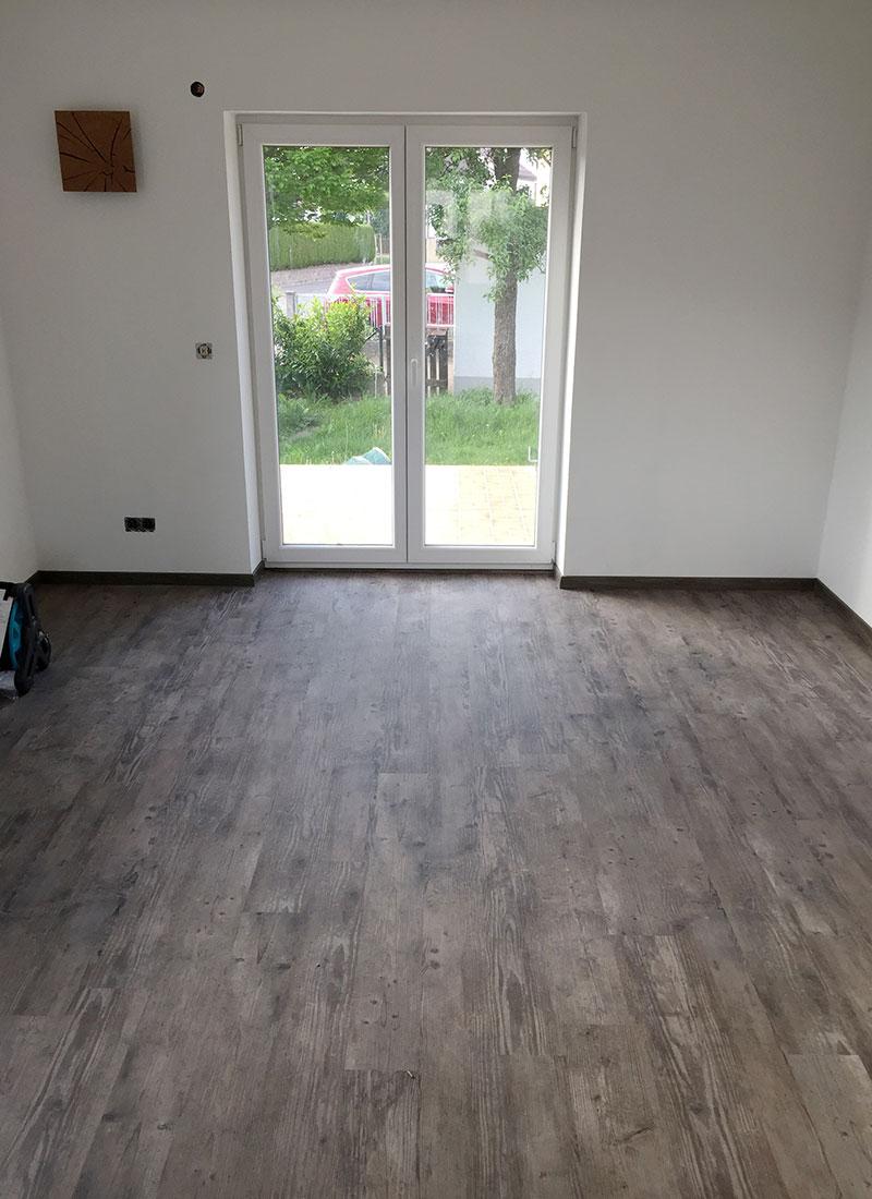 Durch einen neuen Bodenbelag, einen neuen Wandanstrich und neue Fenster wirkt das Wohnzimmer hell und einladend
