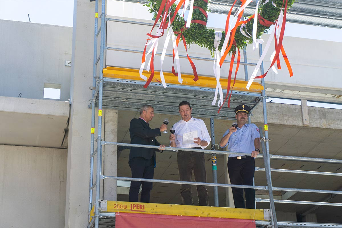 Beim Richtfest erheben Oberbürgermeister, Bauunternehmer und Feuerwehrkommandant die Gläser auf die neue Feuerwache in Günzburg.