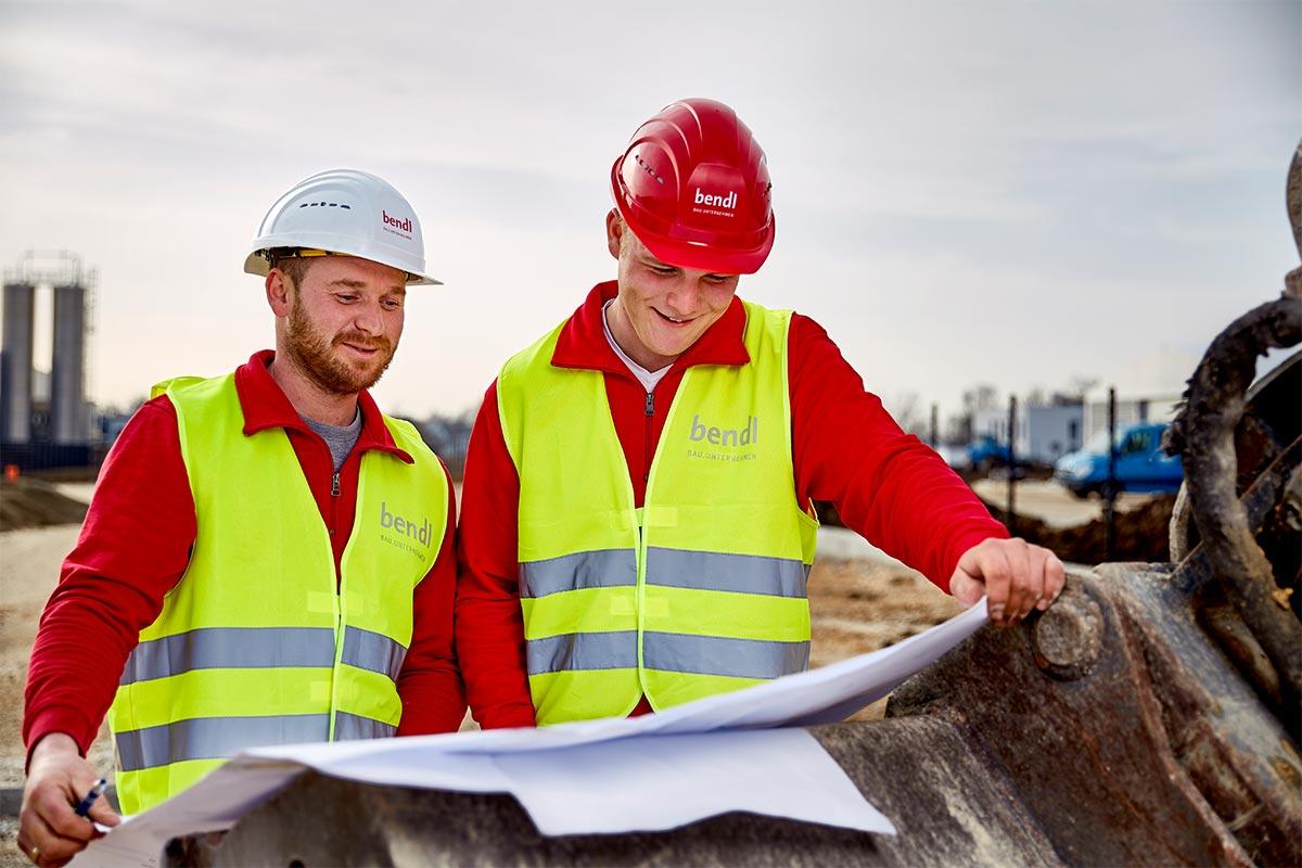 Auszubildender Marcel und Polier Martin besprechen den Grundrissplan. Bauunternehmen bendl Günzburg.